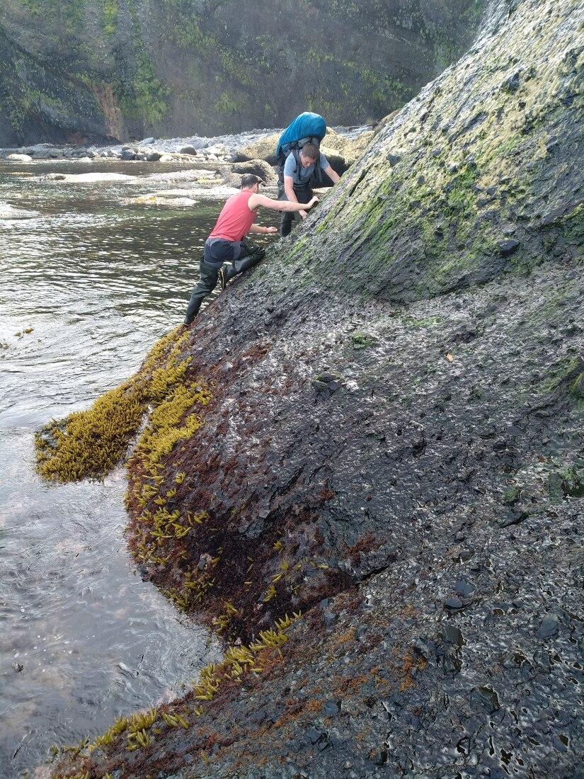 скальный прижим в Охотском море под водопадом в волнах